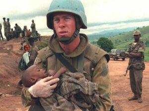 An Australian UN soldier carries a Hutu orphan chi